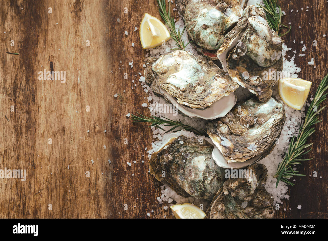 Dozen fresh oysters on the wooden and sea salt. Top view - Stock Image