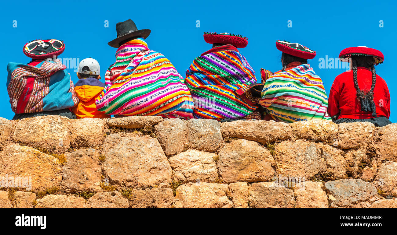 A group of Peruvian Quechua indigenous women in traditional clothing with a boy sitting on an ancient Inca wall in Chincheros near Cusco city, Peru. - Stock Image