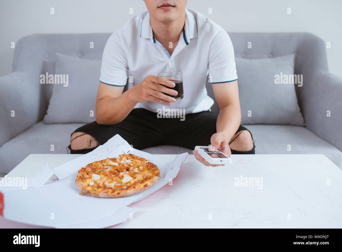 Man watch TV and eating pizza with soft drink. Close up. Sitting on sofa - Stock Image