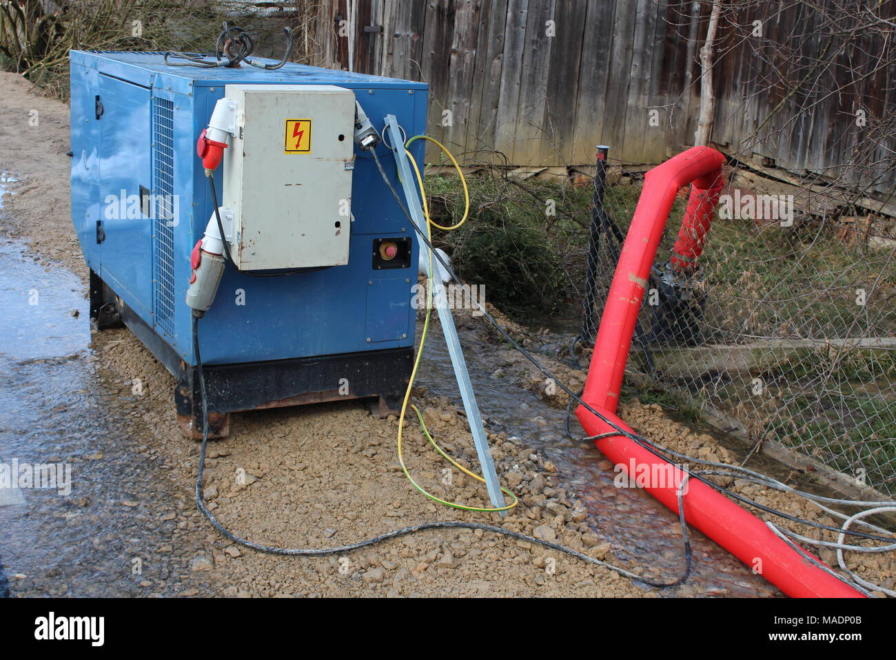 electrical power generator portable enclosed industrial power generator providing electrical to large water pumps with strong red hose pumping over wire fence during flood