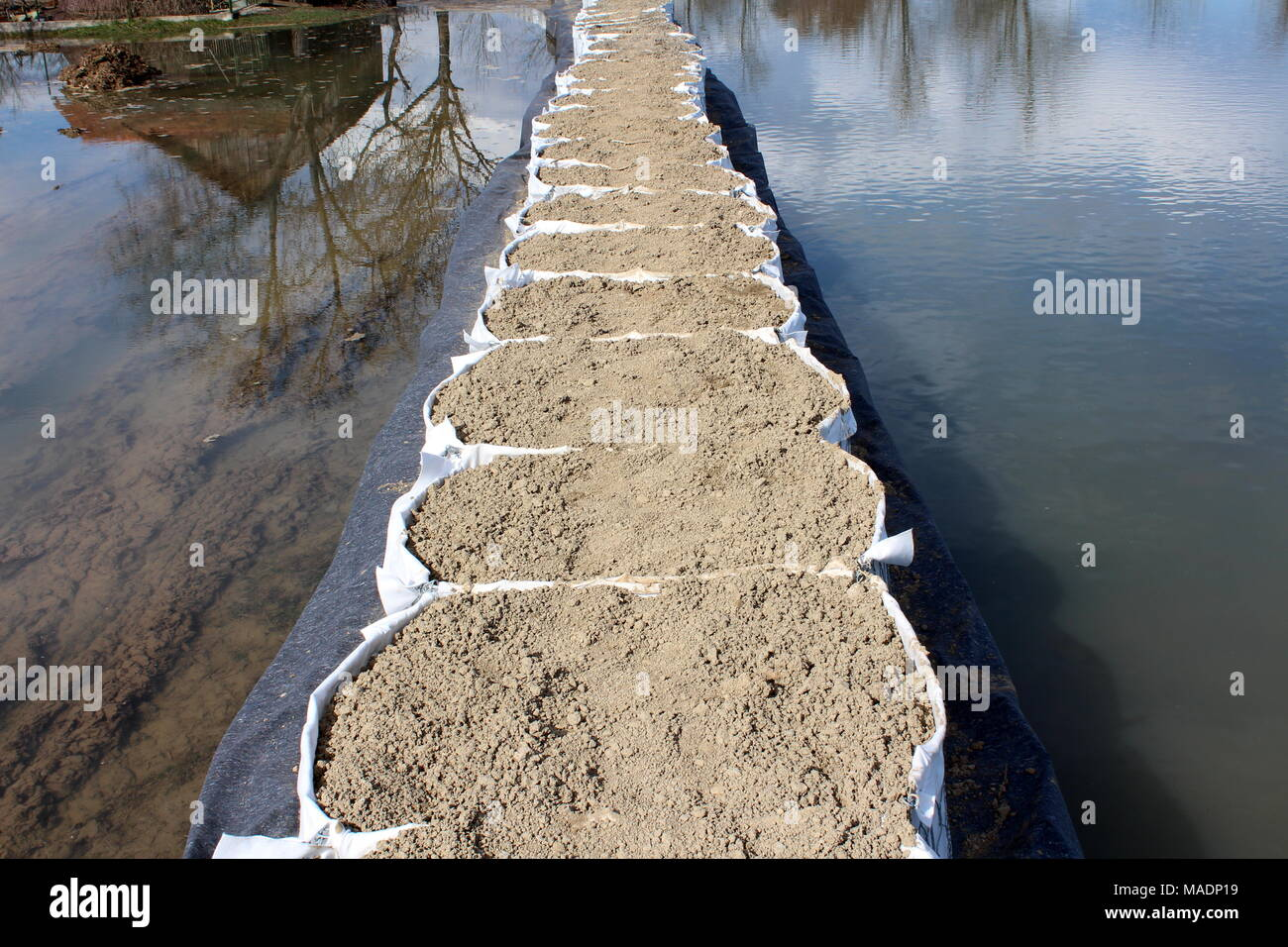 Top view of sandbox barriers flood protection with water reflections of house, trees, clouds and blue sky on cold winter day - Stock Image