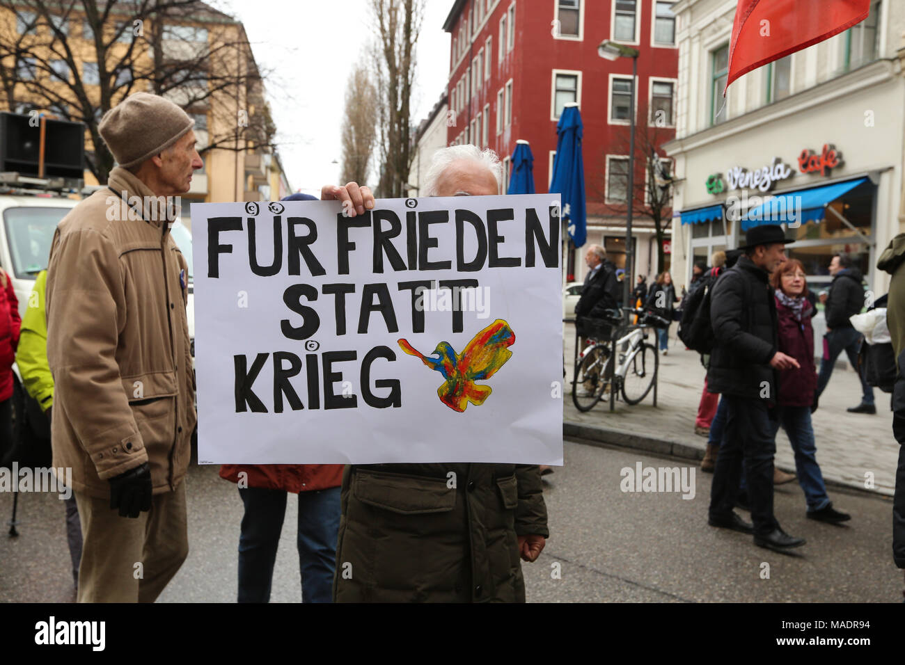 Munich, Germany. 31st Mar, 2018. A man with a sign with a colorful pigeon. Some thousand joined the Ostermarsch (easter march) for peace and disarmament. The Ostermarsch is a traditional peace demonstration, which is held yearly in hundreds of German towns. Credit: Alexander Pohl/Pacific Press/Alamy Live News Credit: PACIFIC PRESS/Alamy Live News - Stock Image