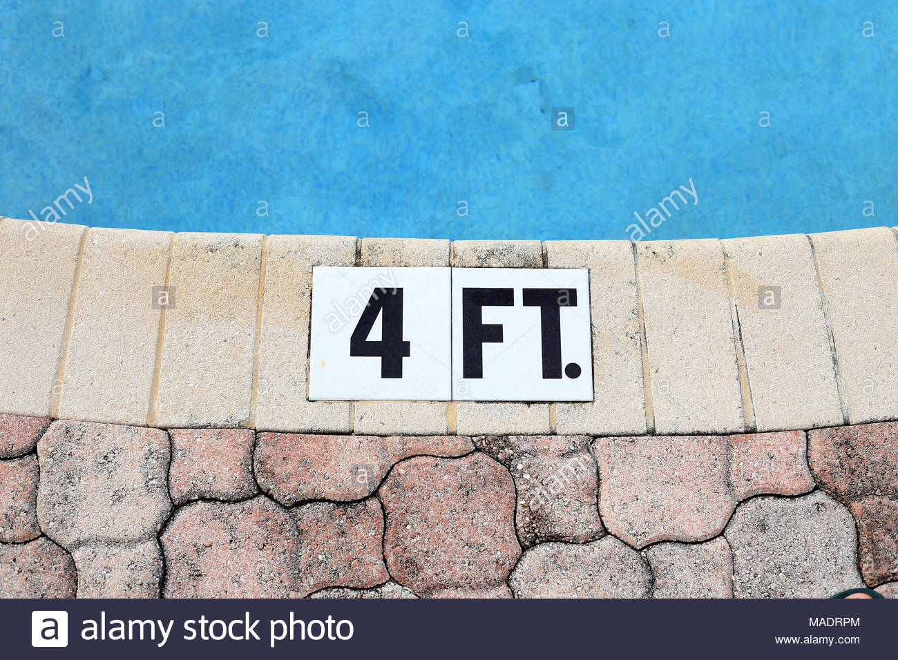 The edge of a shallow swimming pool. Its depth (four feet ...