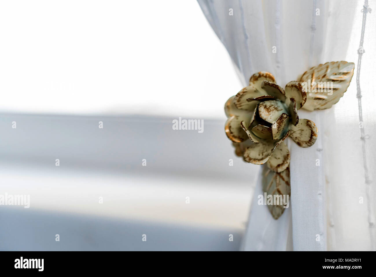 Decorative curtain clip in shape of flower - Stock Image