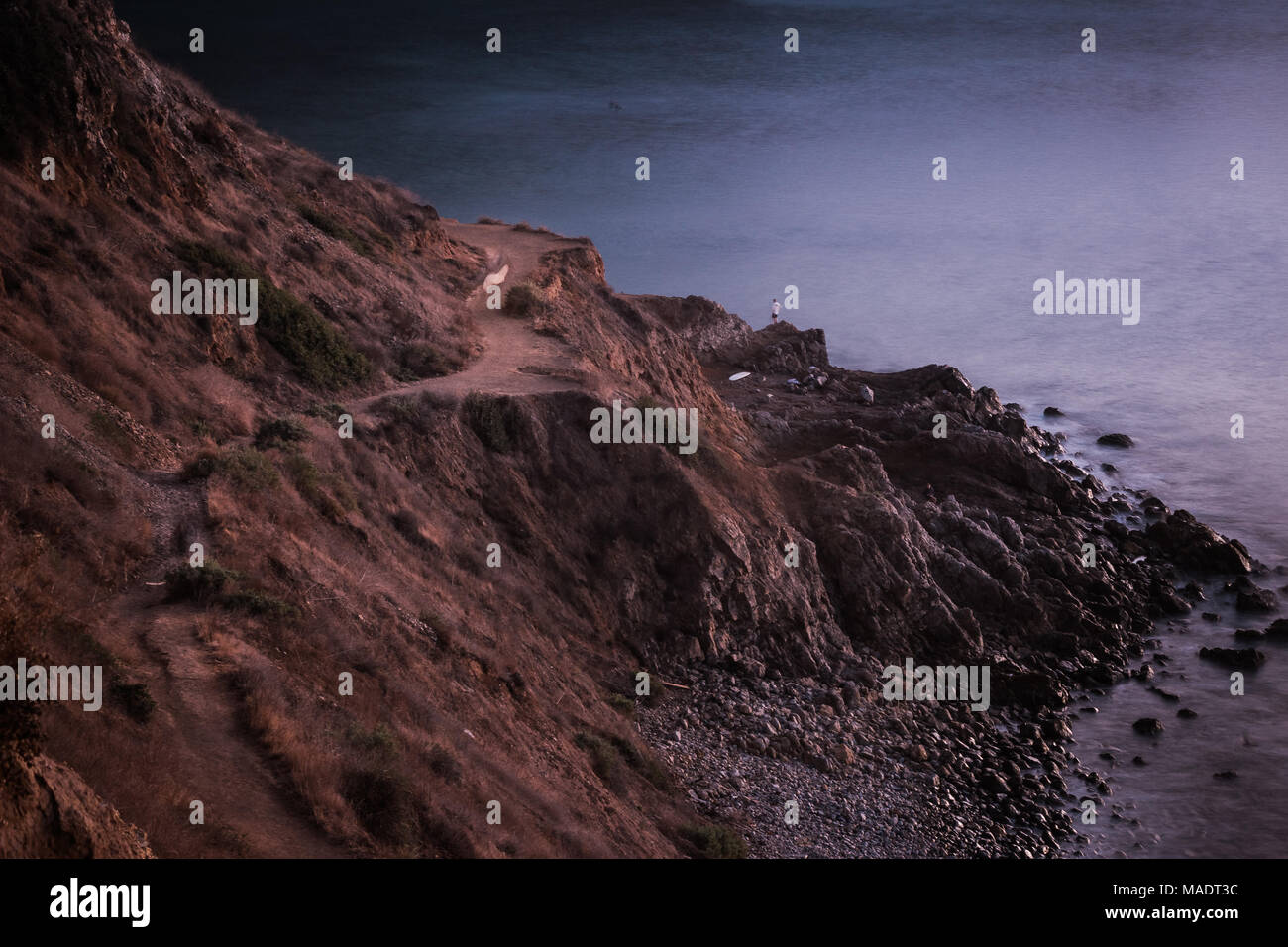 Long-exposure shot of smooth waves crashing into Flat Rock Point rock formations and Bluff Cove Trail after sunset, Palos Verdes Estates, California Stock Photo
