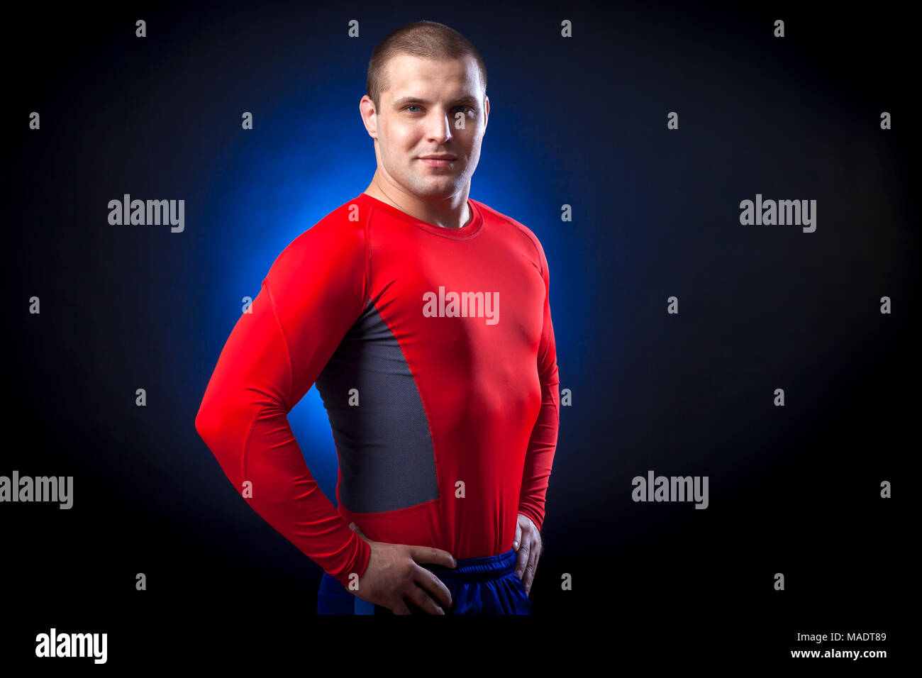 A strong dark-haired sportman  in a red sports wear  rush guard posing against a blue a lights on a black isolated  background - Stock Image