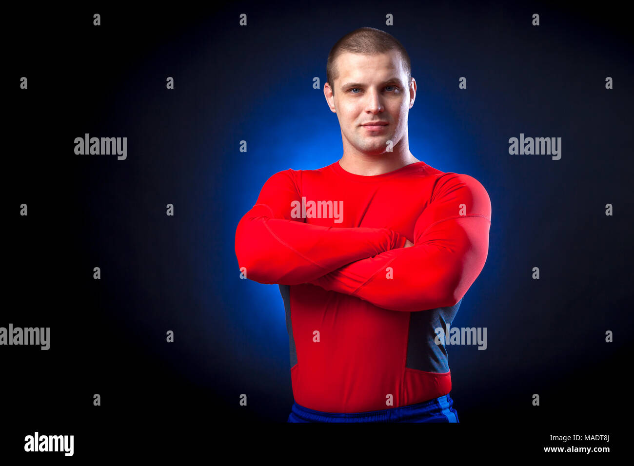 A strong dark-haired sportman  in a red sports wear  rush guard  smile and standing  against a blue a lights on a black isolated  background - Stock Image