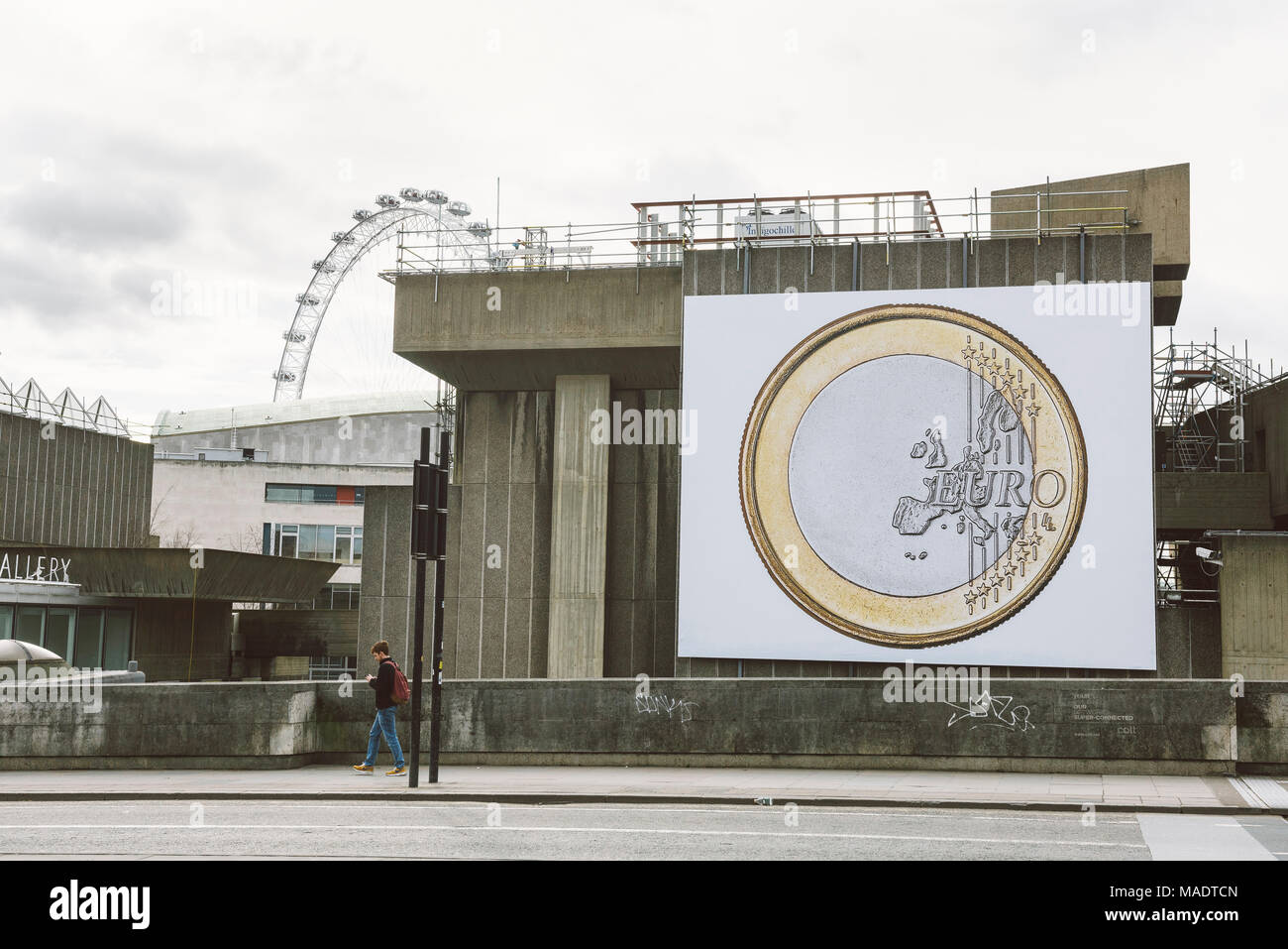 EURO billboard illustrating Euro coin is hanging on the exterior wall outside Queen Elizabeth Hall and Purcell Room building in London, UK. - Stock Image