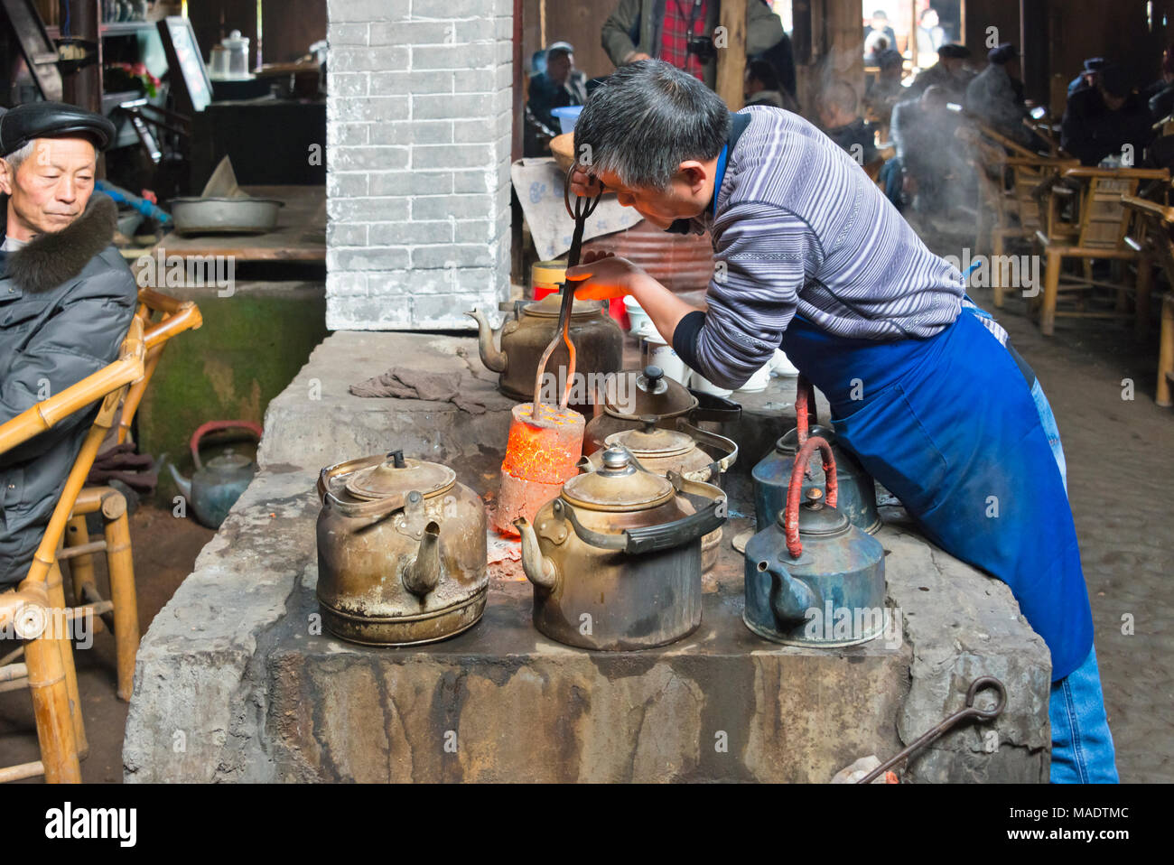 Changing coal briquette in the kitchen of an old tea house, Chengdu, Sichuan Province, China - Stock Image