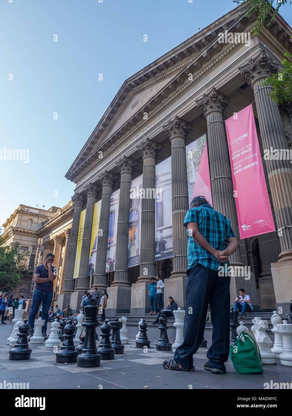 People playing chess on big pavement chess boards in front of the State Library of Victoria with library columns and banners in the background. - Stock Image