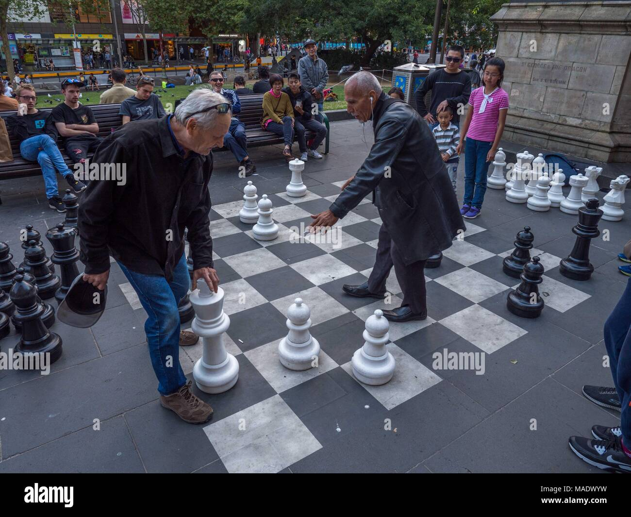 Young asian girl and older man playing chess on outdoor board in front of library.  Young girl moving chess pieces.  Old men arguing over moves. - Stock Image