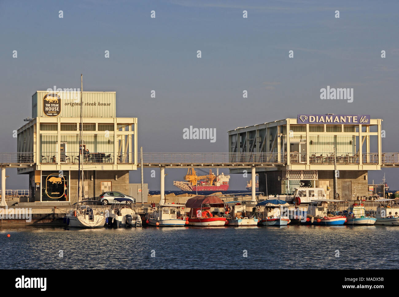 The Steak House and Diamante blu restaurants on quay of harbour, Limassol, Cyprus - Stock Image