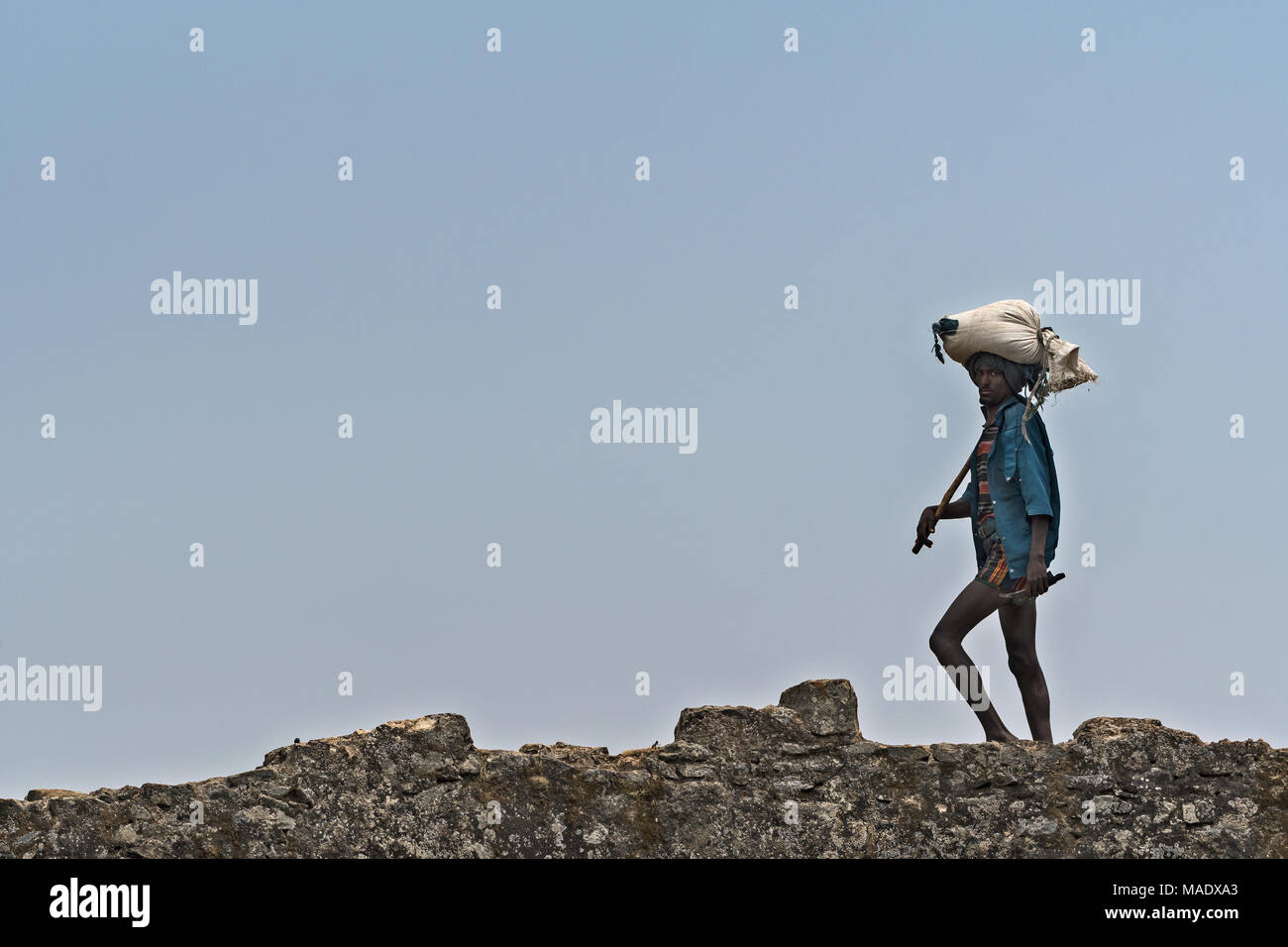 Ethiopian people crossing a stone bridge, Debre Libanos, Ethiopia - Stock Image