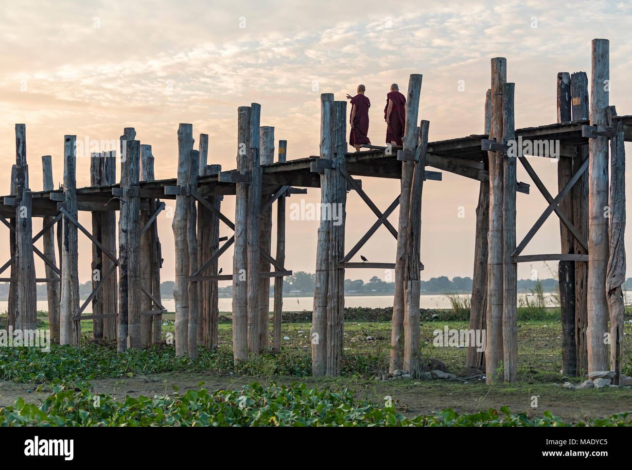 Buddhist monks walk on the U Bein Bridge in Amarapura near Mandalay, Burma (Myanmar) Stock Photo