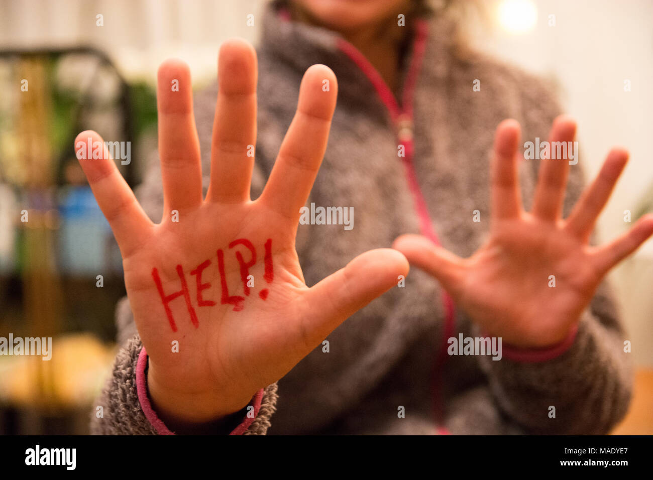 Help! written on woman hand close to the camera. Woman's asks for help writting on his hand. Stock Photo