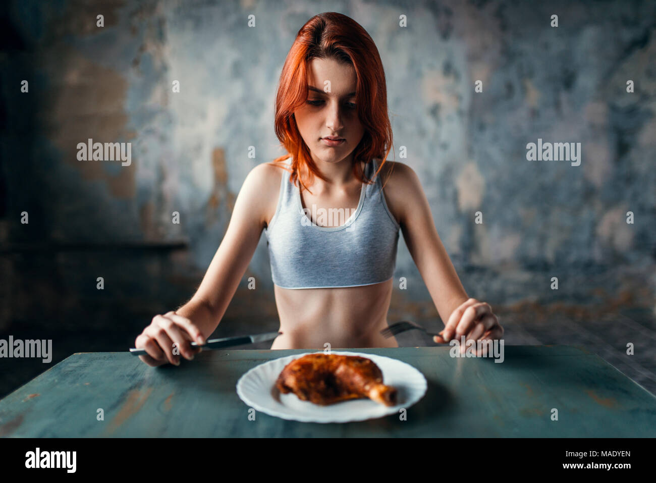 Woman against plate with food, absence of appetite - Stock Image