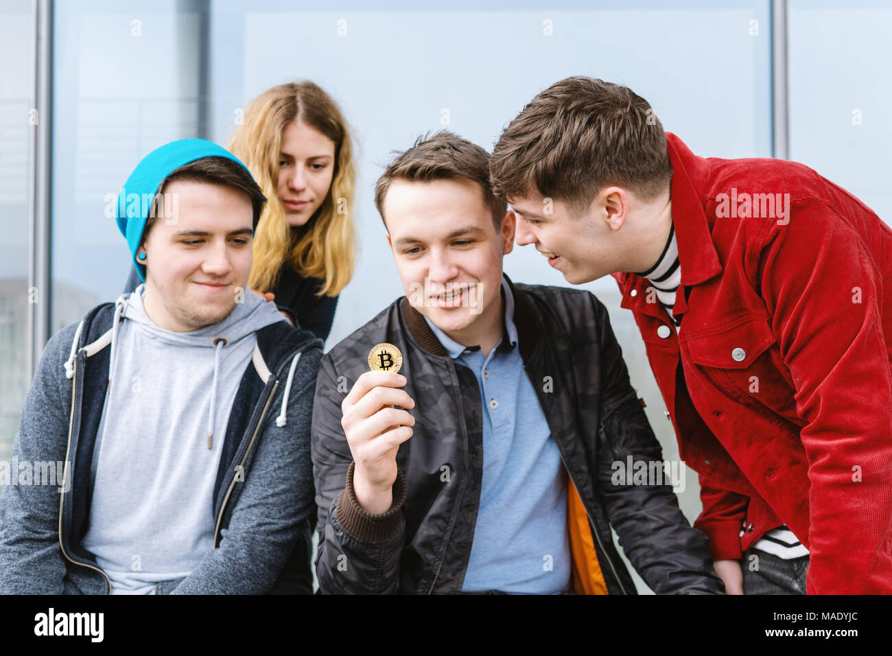 young man showing bitcoin coin to his intrigued group of friends - Stock Image