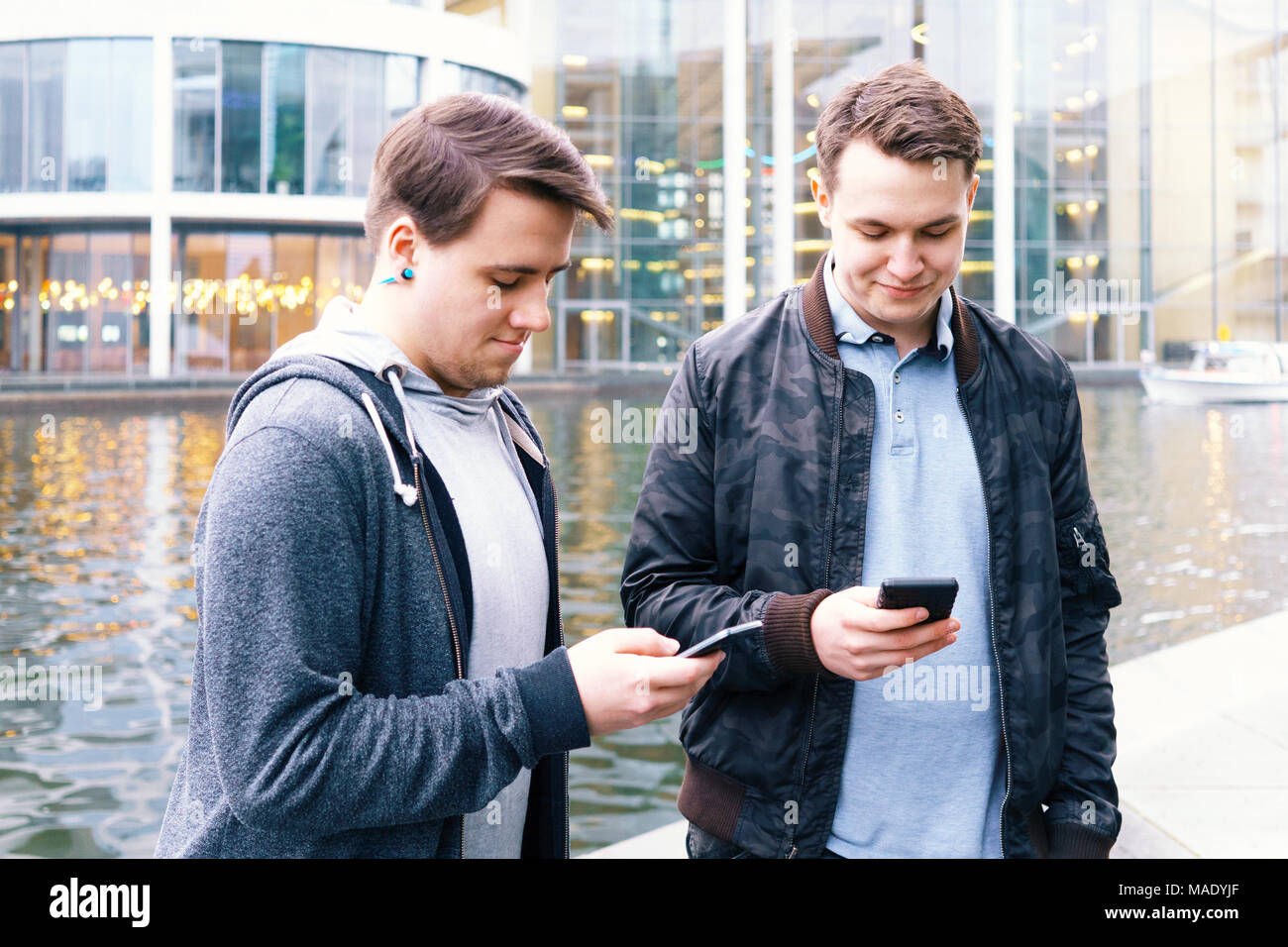 two mobile phone addicted male teenagers standing together looking at smartphone - Stock Image