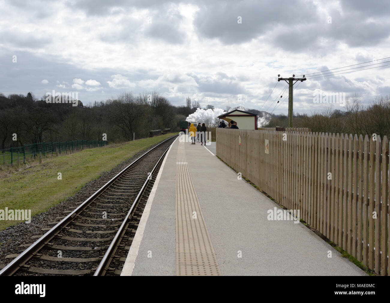 Steam train approaching platform with passengers waiting to board on the east lancashire railway Burrs country park station in Bury lancashire uk - Stock Image