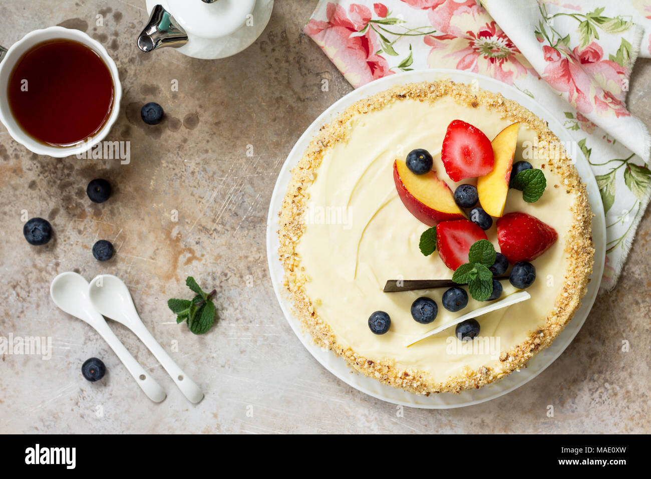 Delicious dessert cake with fresh berries and whipped cream, sweet delicious holiday cake with blueberries and strawberries on stone background. - Stock Image