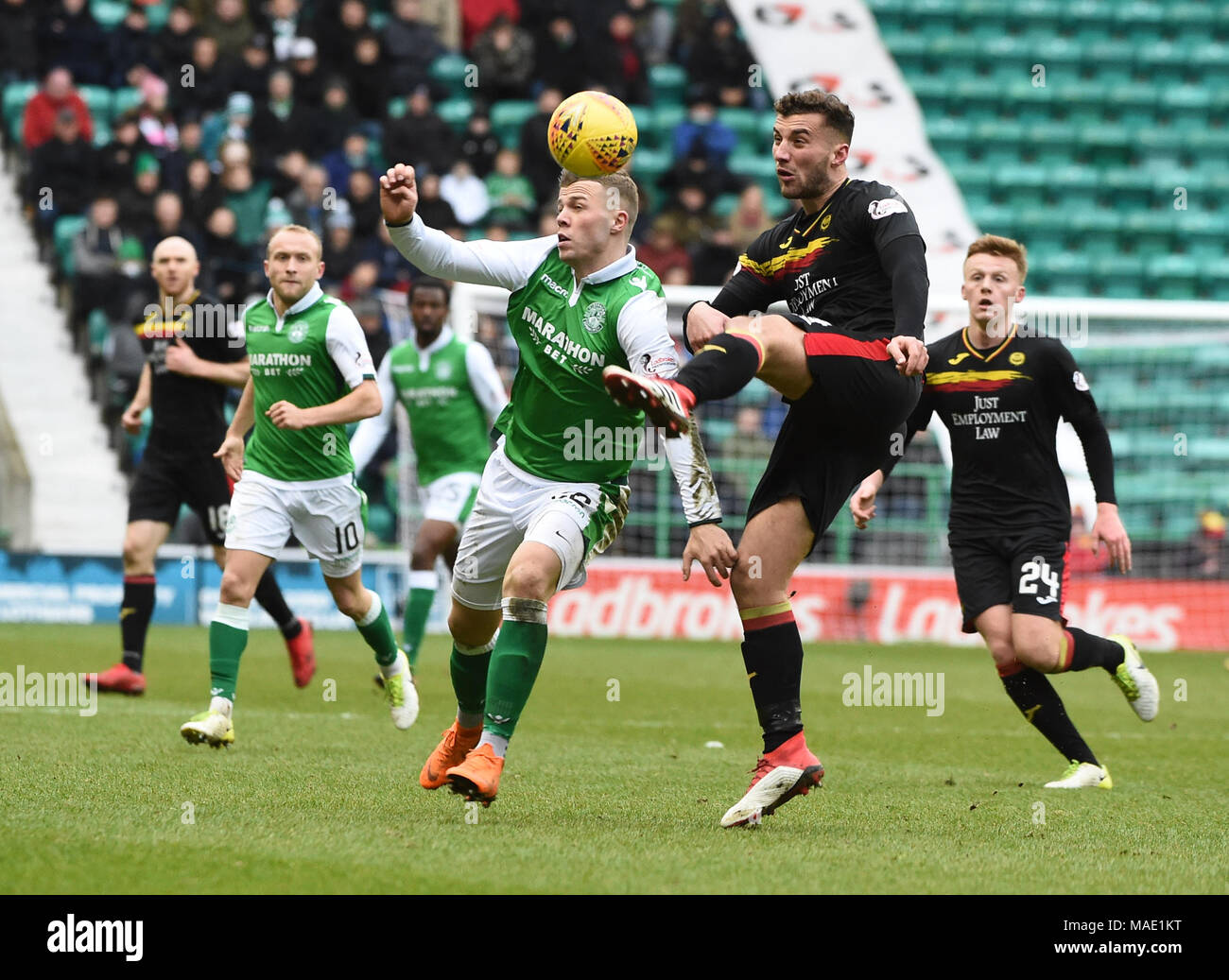 Scottish Premiereship, Hibernian v Partick Thistle, Edinburgh, Midlothian, UK. 31,03, 2018. Pic shows:  Partick Thistle defender, Baily Cargill, clears despite being under pressure from Hibs' Florian Kamberi during the second half of the Scottish Premiereship clash between Hibernian and Partick Thistle at Easter Road Stadium, Edinburgh.  Credit: Alamy/Ian Jacobs - Stock Image