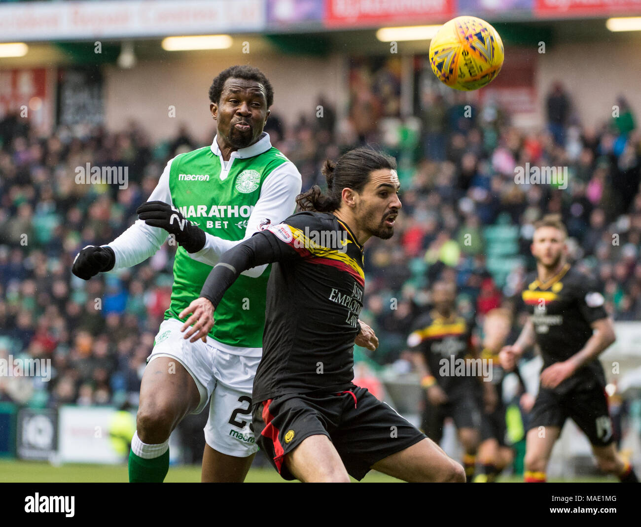 Scottish Premiereship, Hibernian v Partick Thistle, Edinburgh, Midlothian, UK. 31,03, 2018. Pic shows:  Hibs defender, Efe Ambrose, beats Partick Thistle midfielder Ryan Edwards to the ball during the second half of the Scottish Premiereship clash between Hibernian and Partick Thistle at Easter Road Stadium, Edinburgh.  Credit: Alamy/Ian Jacobs - Stock Image