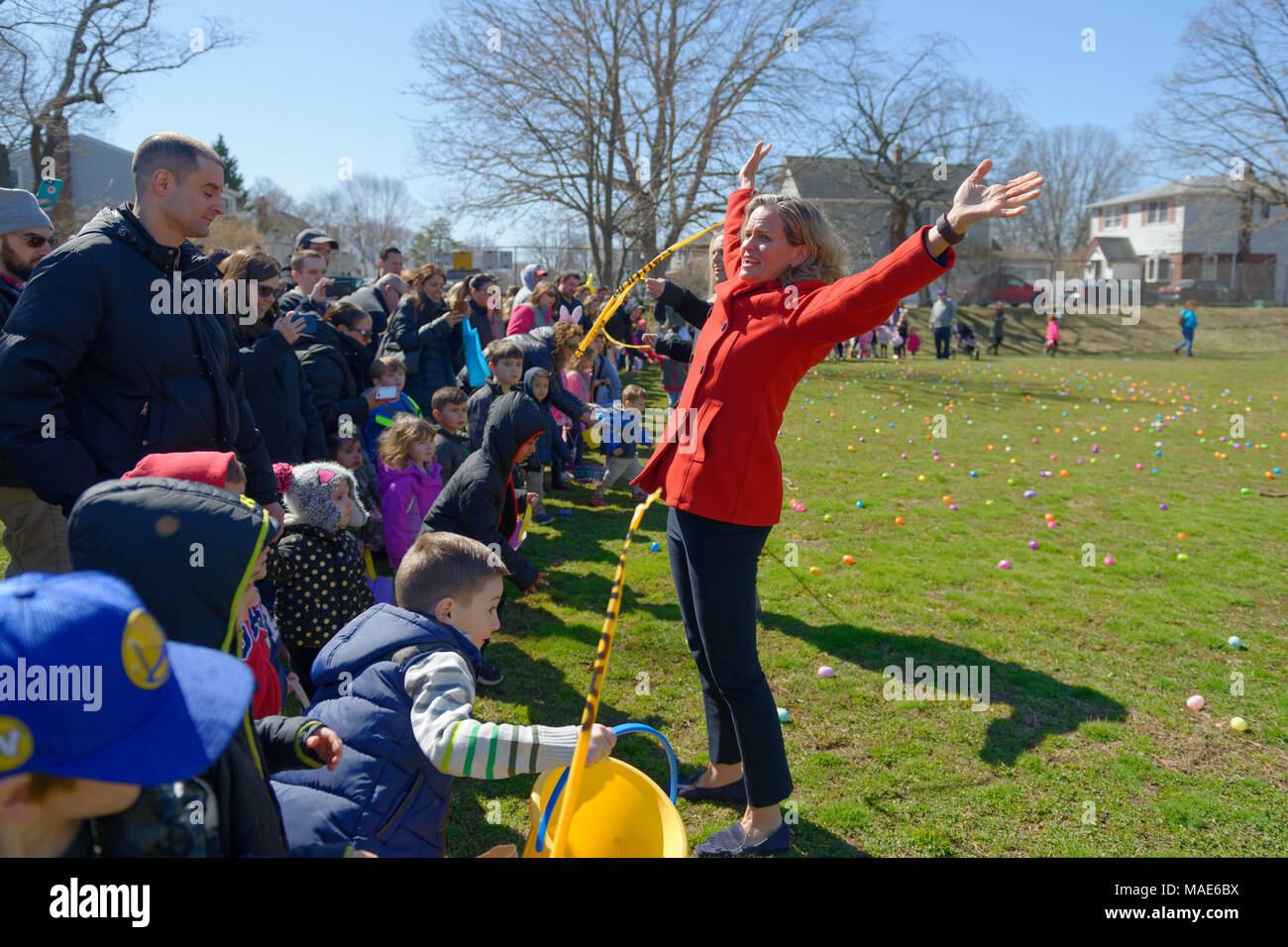North Merrick, New York, USA. 31st Mar, 2018. Nassau County Executive LAURA CURRAN flings her arms up high after cutting the yellow tape to start the Egg Hunt at the Annual Eggstravaganza, held at Fraser Park and hosted by North and Central Merrick Civic Association (NCMCA) and Merrick's American Legion Auxiliary Unit 1282. Young children rush to collect eggs in their Easter baskets. Credit: Ann Parry/ZUMA Wire/Alamy Live News - Stock Image