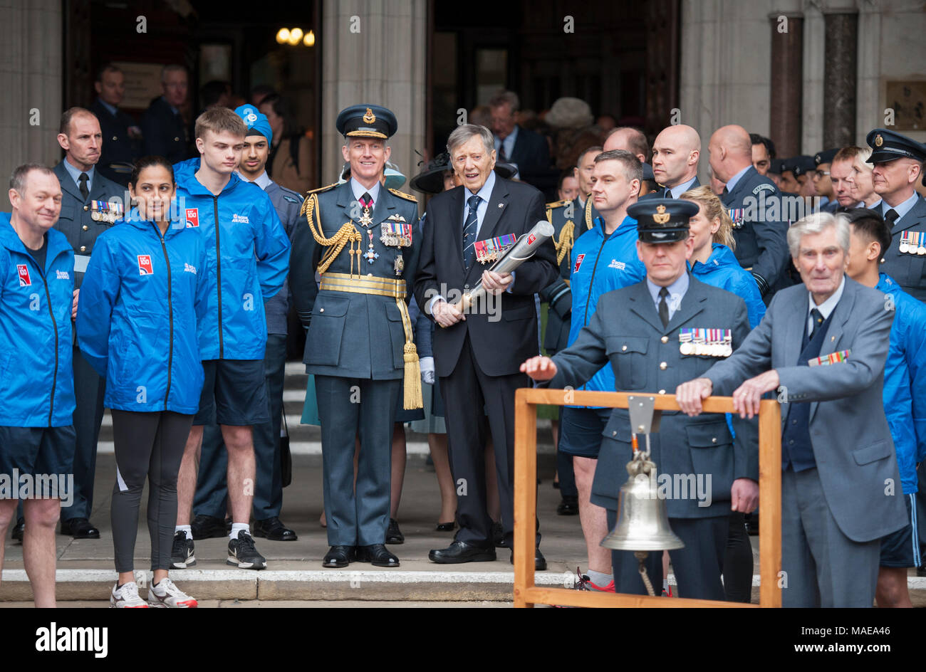 """Royal Courts of Justice, London, UK. 1 April 2018. The RAF100 Baton Relay is launched at the main entrance of the Royal Courts of Justice. The steps are lined with Royal Air Force Air Cadets as the Chief of the Air Staff accompanies distinguished Royal Air Force veteran, Air Commodore (retd) Charles Clarke, carrying the RAF100 Baton. A Scramble Bell is sounded by esteemed veteran and one of the """"Few"""" Wing Commander (retd) Paul Farnes (right), a former Battle of Britain fighter pilot, to signal the launch of the relay. Credit: Malcolm Park/Alamy Live News. - Stock Image"""