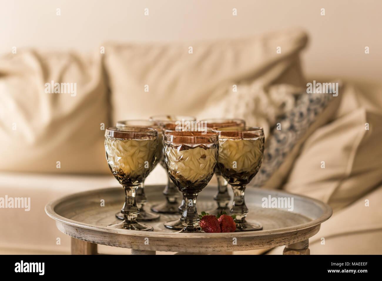 Tiramisu in elegant glasses on round metal table in beige interior.  Horizontal composition.  Narrow depth of field. - Stock Image