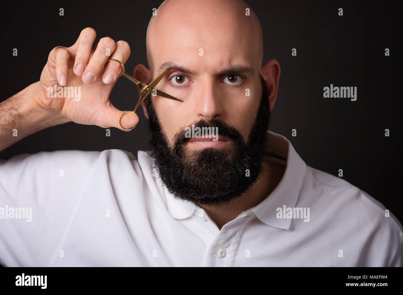 Portrait of bald bearded man holding scissors on his eye over dark background Stock Photo