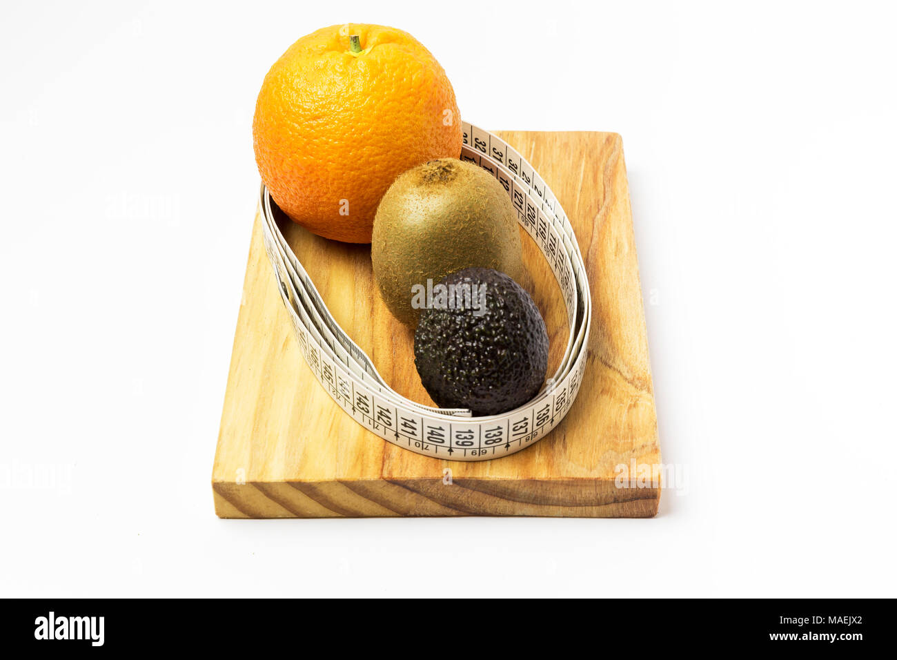 orange, kiwi and avocado surrounded by a tape measure on a wooden board - Stock Image