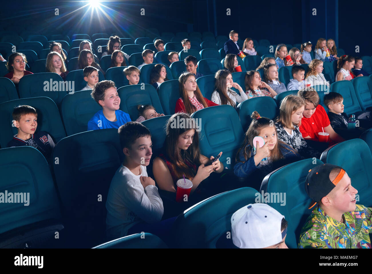 Schoolmates watching movie in the cinema. Boys and girls looking happy,emotional, funny and satisfied. Children wearing colorful clothes. Eating popcorn and drinking fizzy drinks. - Stock Image