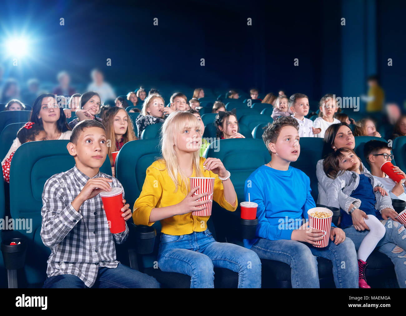 frontview of little exited children watching interesting movie in cinema hall. Boys and girls look very emotional and happy. schoolmates wearing colorful clothes,eating popcorn, drinking fizzy drinks. - Stock Image