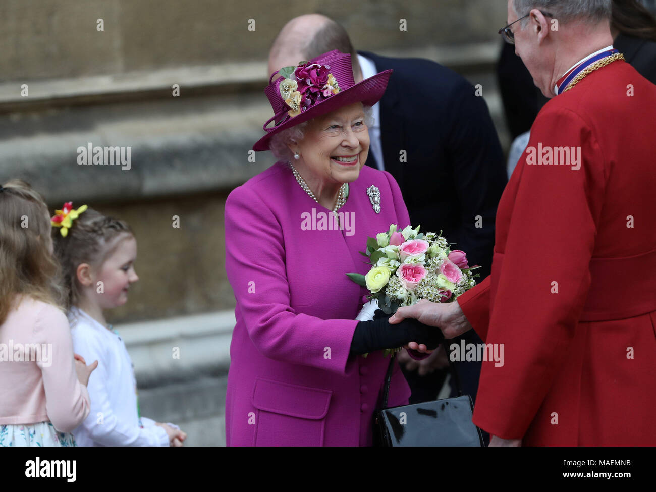 Queen Elizabeth II holds a posey as she leaves following the Easter Mattins Service at St George's Chapel, Windsor Castle, Windsor. - Stock Image