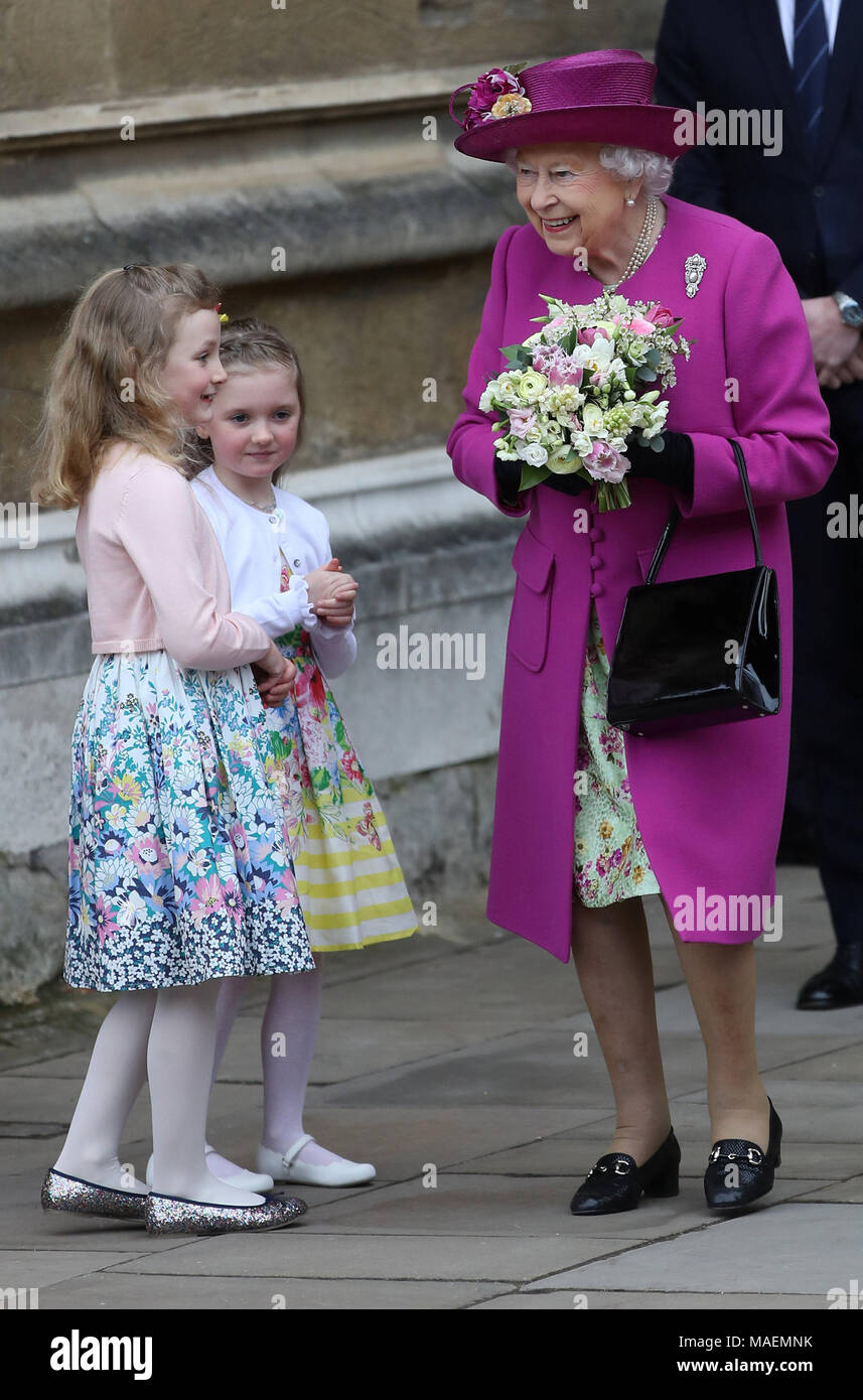Queen Elizabeth II is handed a posey as she leaves following the Easter Mattins Service at St George's Chapel, Windsor Castle, Windsor. - Stock Image