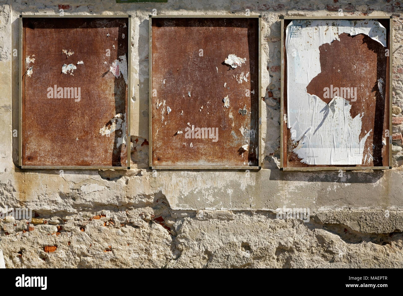 Three old rusty noticeboard frames on stone wall, Cuneo, Italy. - Stock Image