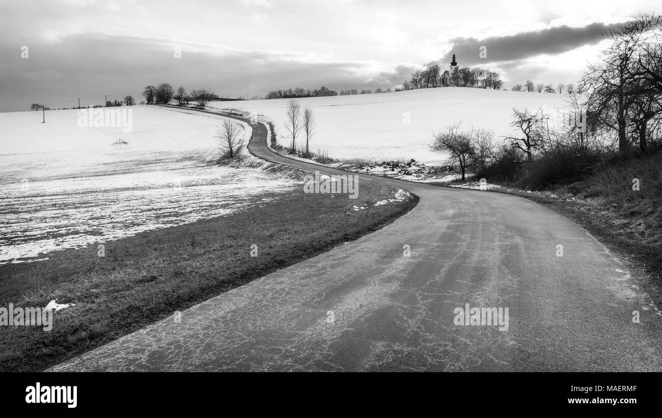 Scenic black and white landscape with a chapel on the horizon. Artistic wintry scene with country road, snowy field and the church on hillock. - Stock Image