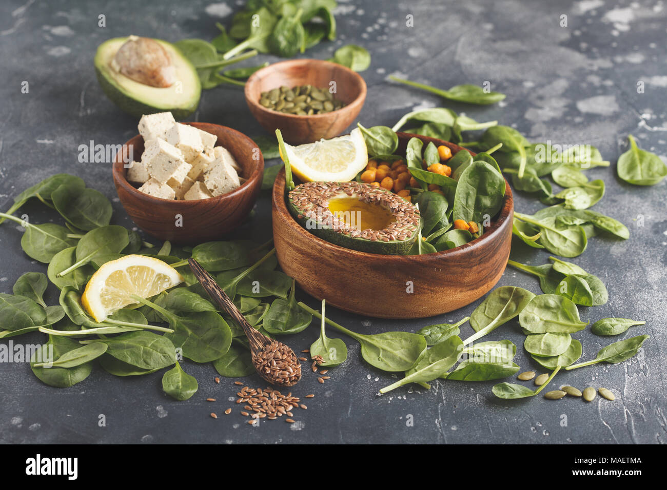 Healthy vegetarian salad with tofu, chickpeas, avocado and sunflower seeds. Healthy vegan food concept. Dark background, copy space. Stock Photo