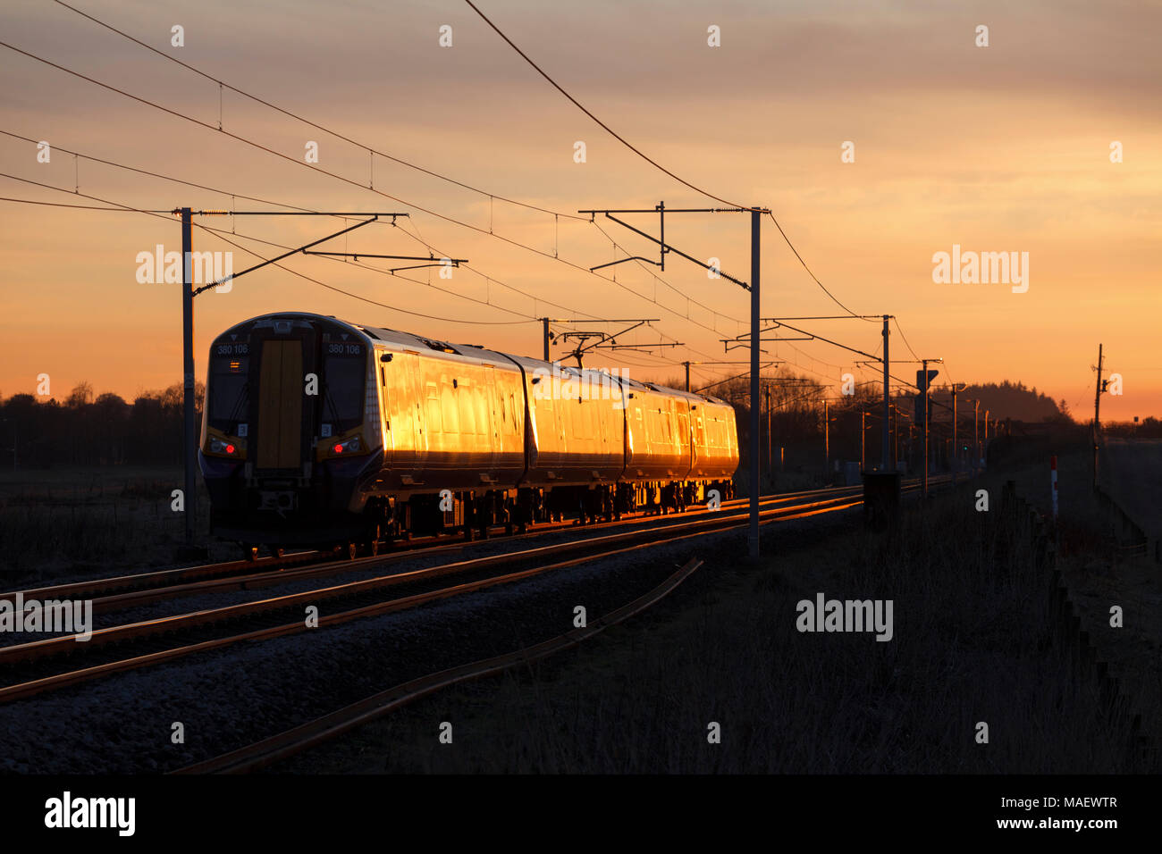 Scotrail class 380 electric train glinting in the sunset 380106  passes Ravenstruther (Carstairs ) with the 1740 Edinburgh Waverley - Ayr - Stock Image