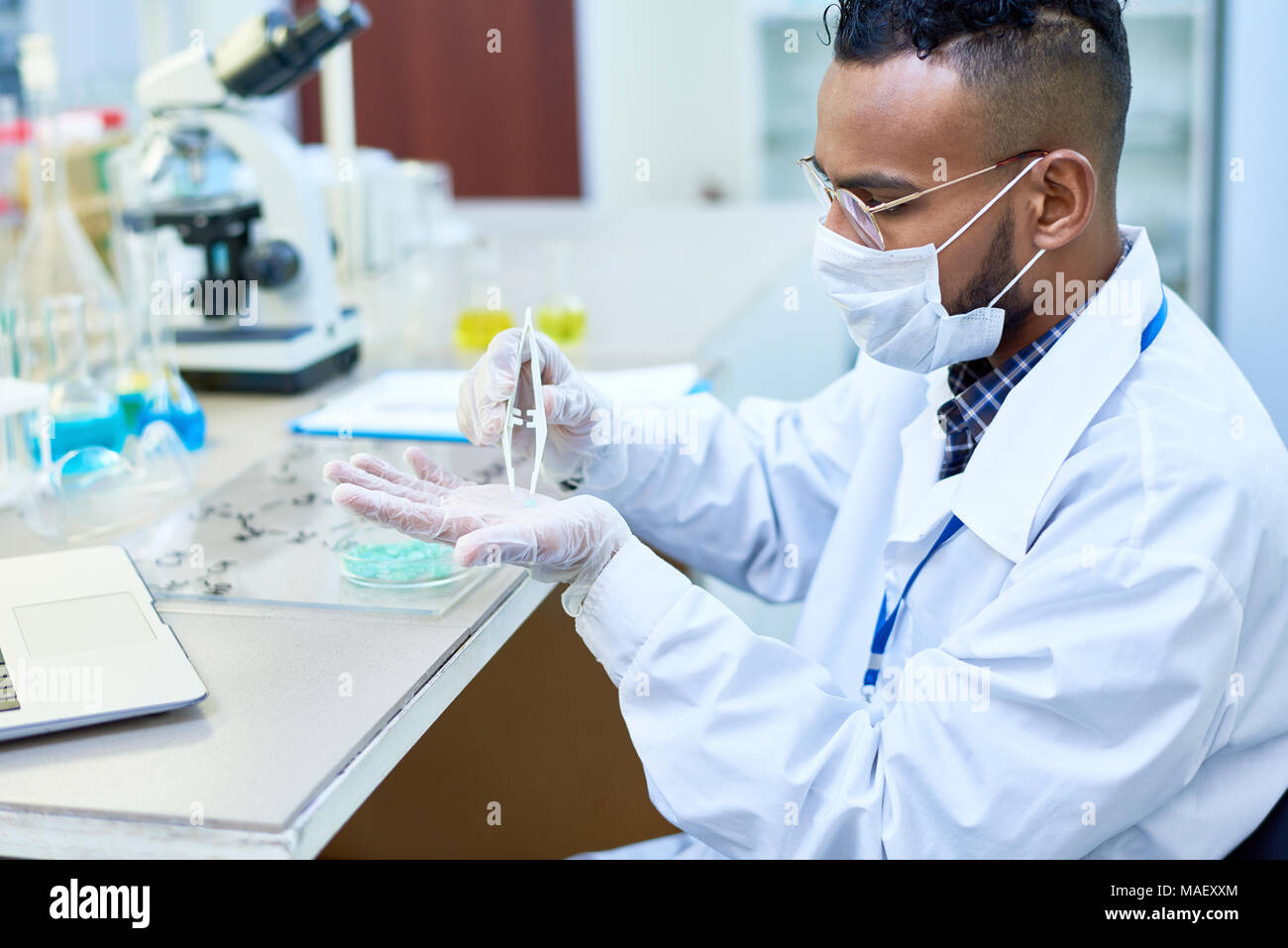 Concentrated handsome chemist analyzing medical sample - Stock Image