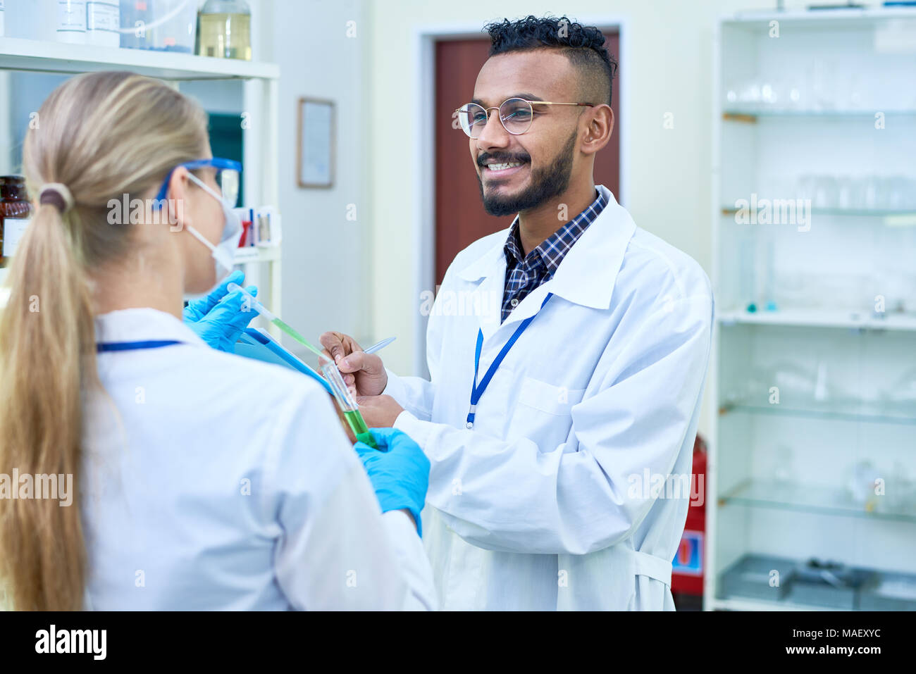 Cheerful laboratory employees discussing experiment Stock Photo