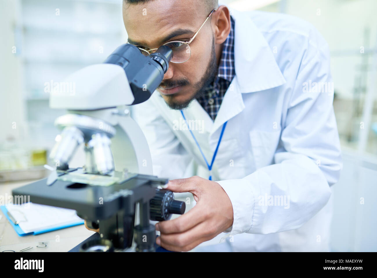 Modern handsome biologist adjusting microscope to zoom image - Stock Image