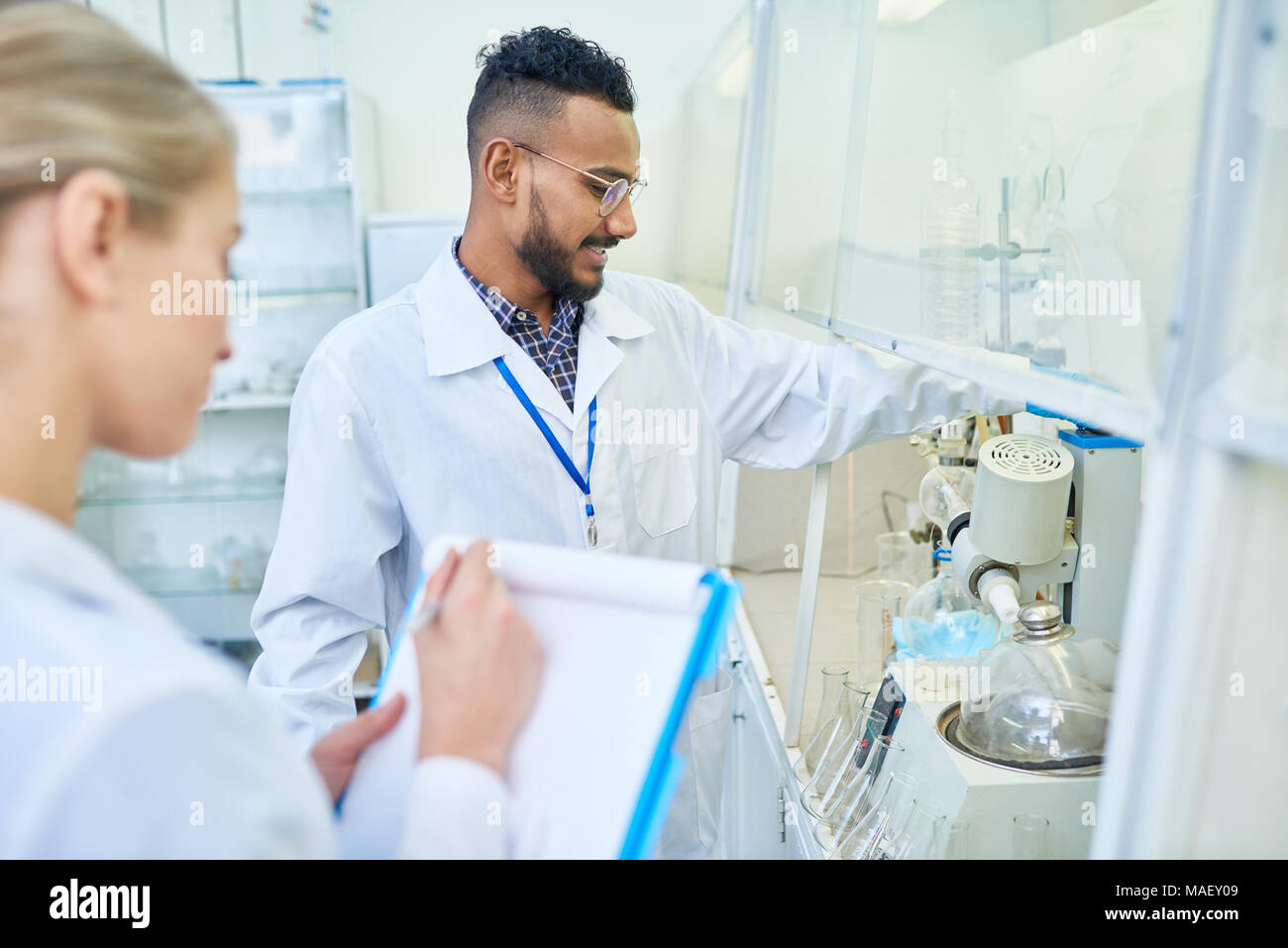 Cheerful researcher and his assistant using laboratory equipment Stock Photo