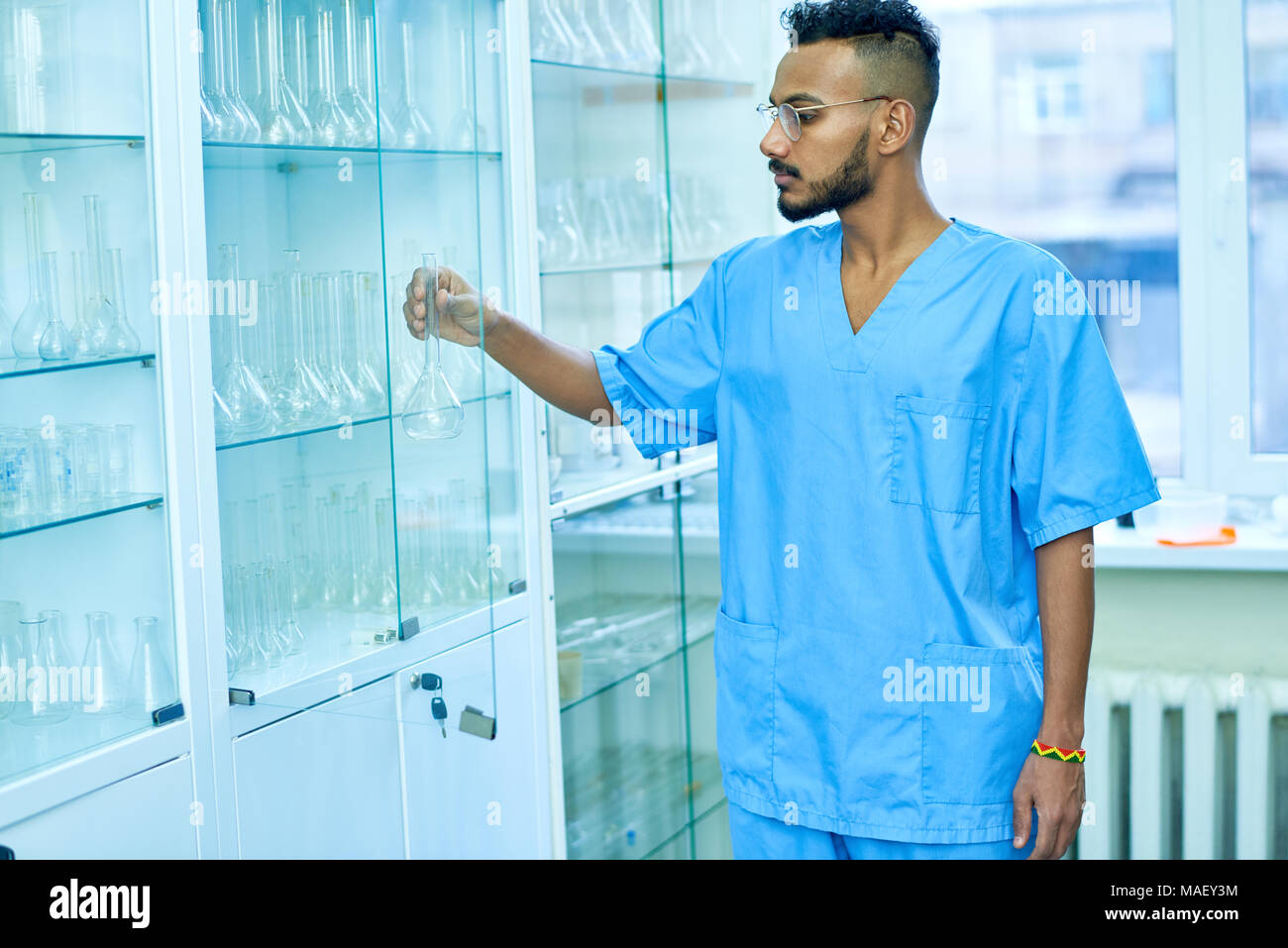Handsome man working in clean laboratory - Stock Image