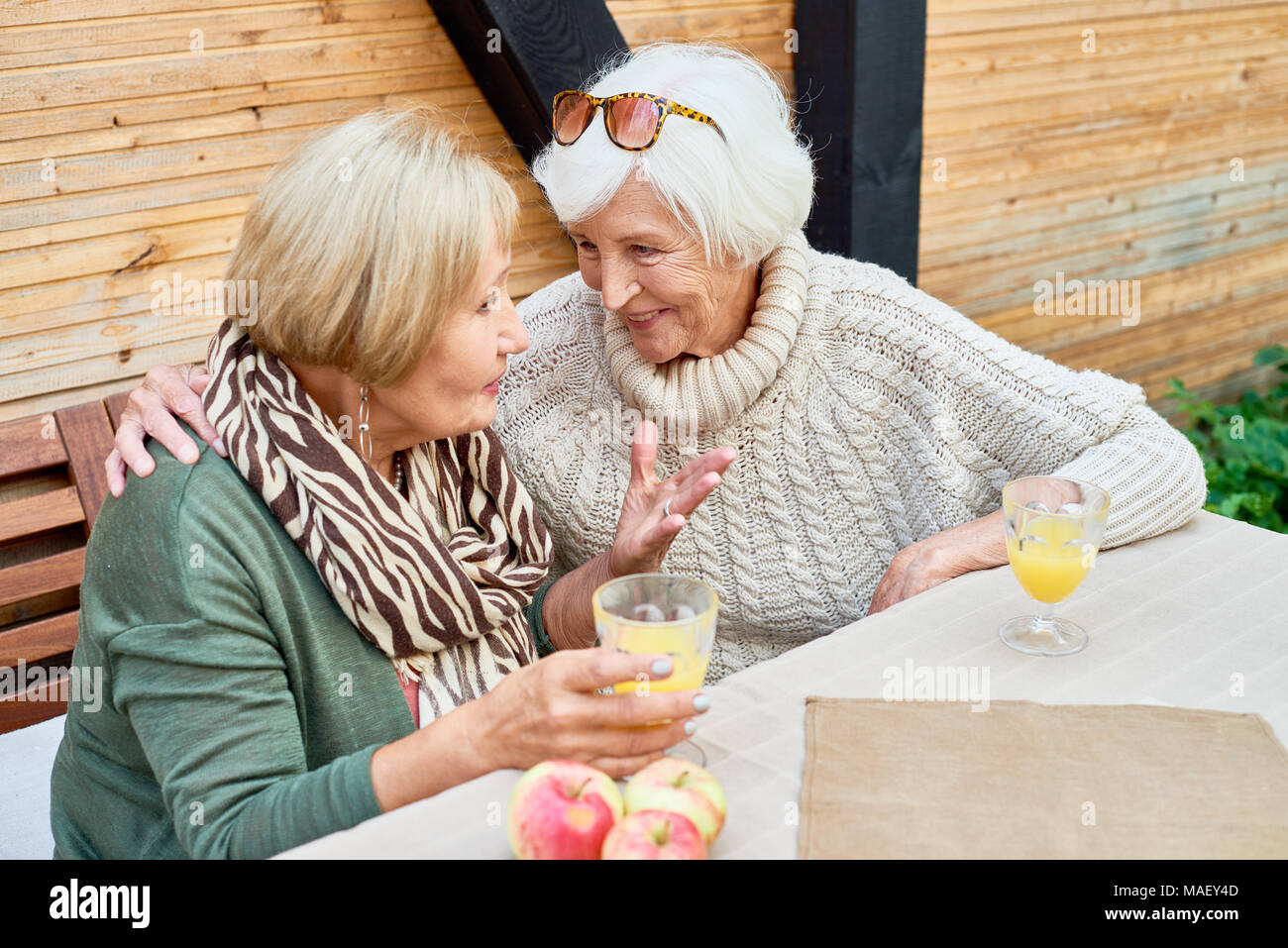 Senior Girlfriends in Cafe Together - Stock Image