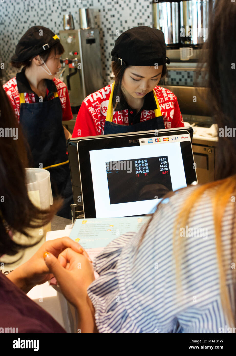 Employee at a fast food outlet's cash register in Melbourne's CBD, which has its display entirely in Chinese. - Stock Image