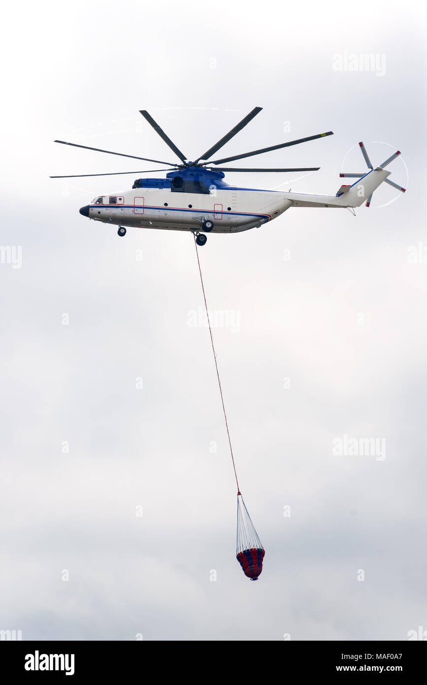Fire helicopter flies in sky and has a water tank for fire fighting - Stock Image