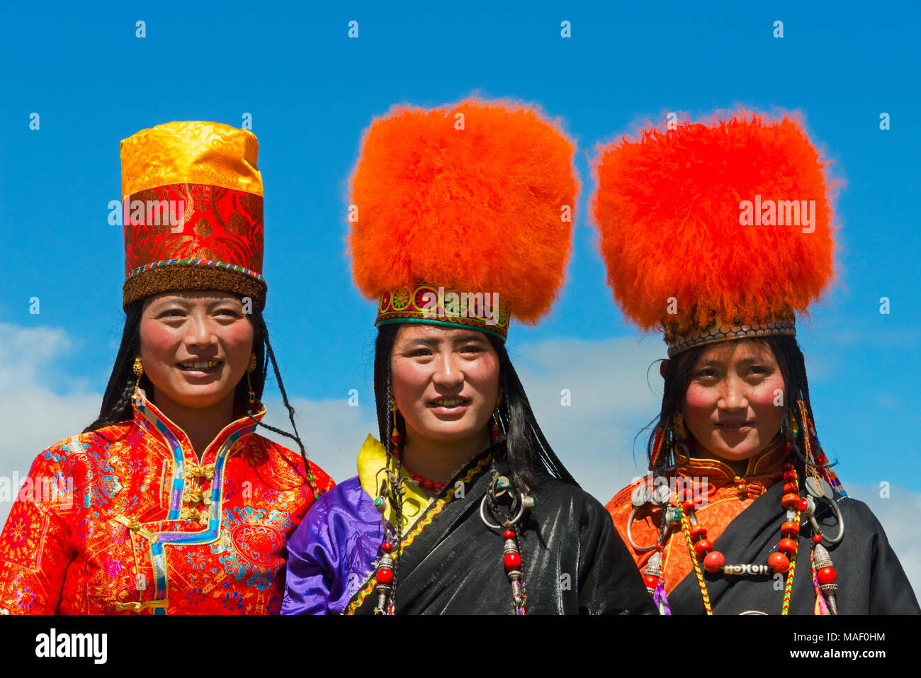 Tibetan women in traditional clothing at Horse Race Festival, Litang, western Sichuan, China - Stock Image