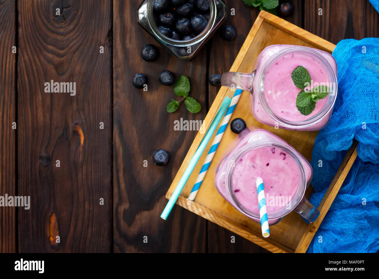 Mason jar mugs with fresh berry cocktails blueberry. Diet, concept of vegetarian food. Proper nutrition. - Stock Image