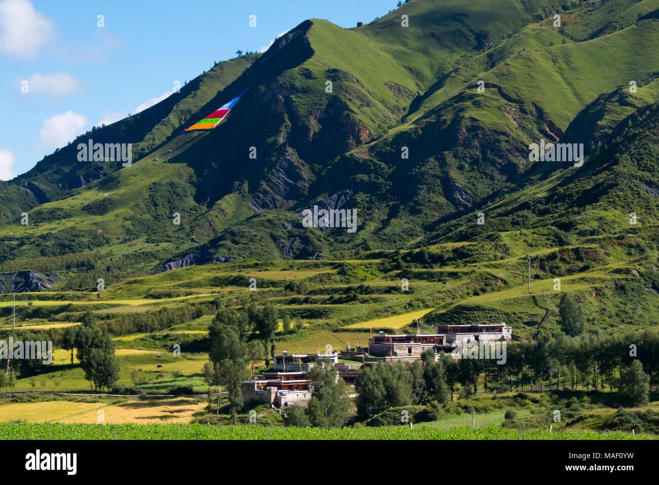 Praying flags on the hillside, Tibetan village house and farmland, Bamei, Garze Tibetan Autonomous Prefecture, western Sichuan, China Stock Photo